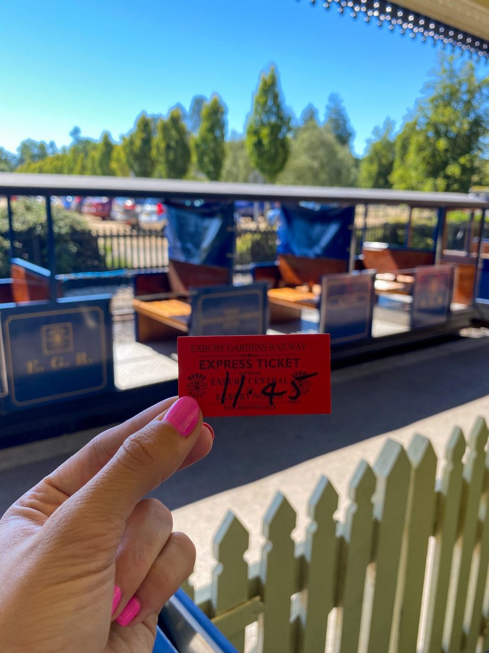 train ticket held up in front of steam train