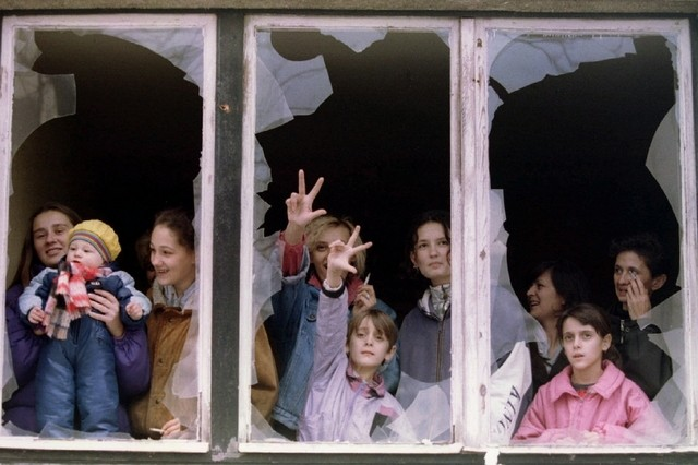 Serbian women and children watch protesters from the shattered windows of an apartment building in Sarajevo in 1995. (Reuters file)
