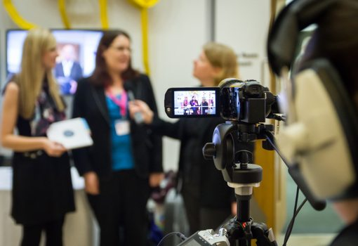 Camera pointed at interviewer and two interviewees at a conference stand