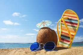 Photo of a spot at the beach with a chair, sunglasses, coconut drink with an umbrella