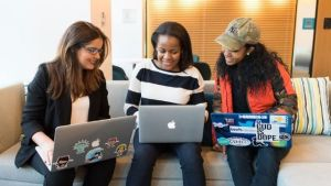 Three women sitting next to each other using their laptops
