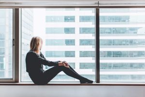 A woman staring out of an office building window