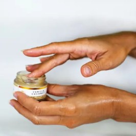 One hand is holding an open jar of cleansing balm, while the other hand is applying product with fintertips.