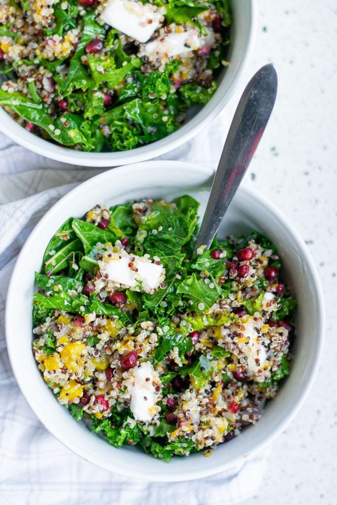 Roasted kale quinoa pumpkin salad in a white bowl.