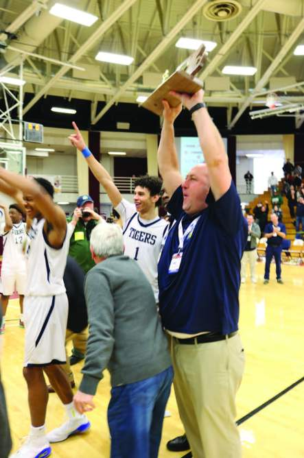 Tigers' head coach Leo Boucher raises the Pope John's first ever State Championship trophy following the blowout win.
