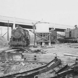 April 1954: After the H&BT closed, #38 was used by Hyman-Michaels, the railroad's dismantler, as power for the scrap train.  Here, she rests at the Long Siding Yard alongside cranes 2 and 3.  James Lilly, Photograph; Collection of Keith Burkey