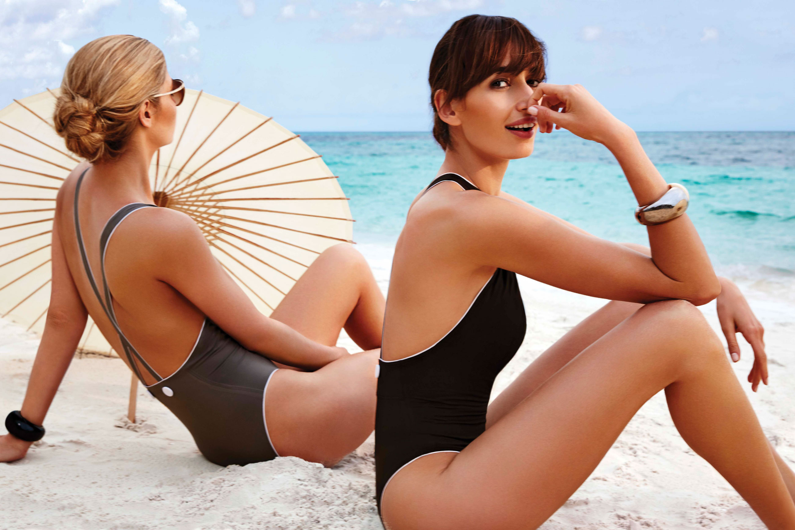 Women on beach in retro one piece swimsuits