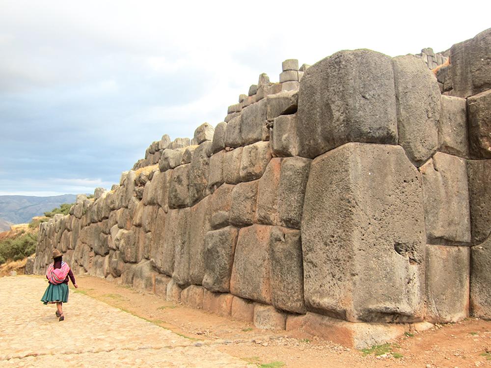 Woman walks by stone wall in Cusco, Peru