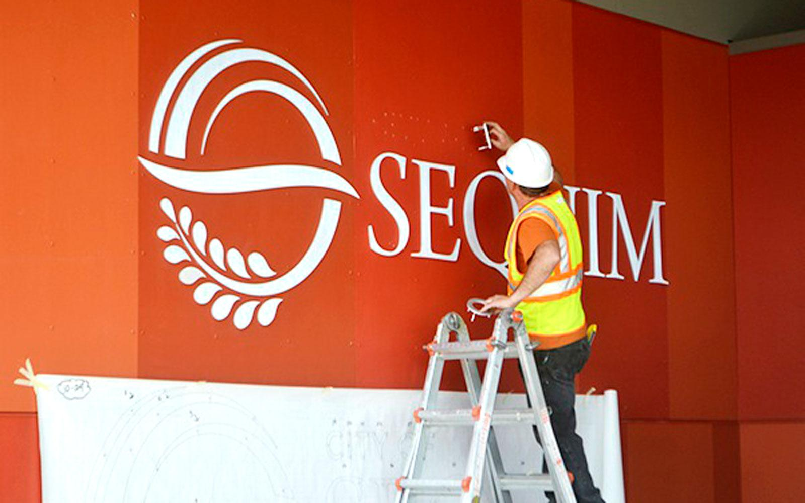 The installer works to make sure the lettering and logo emblem is lined up right right within the paint work and panels on this building installation.