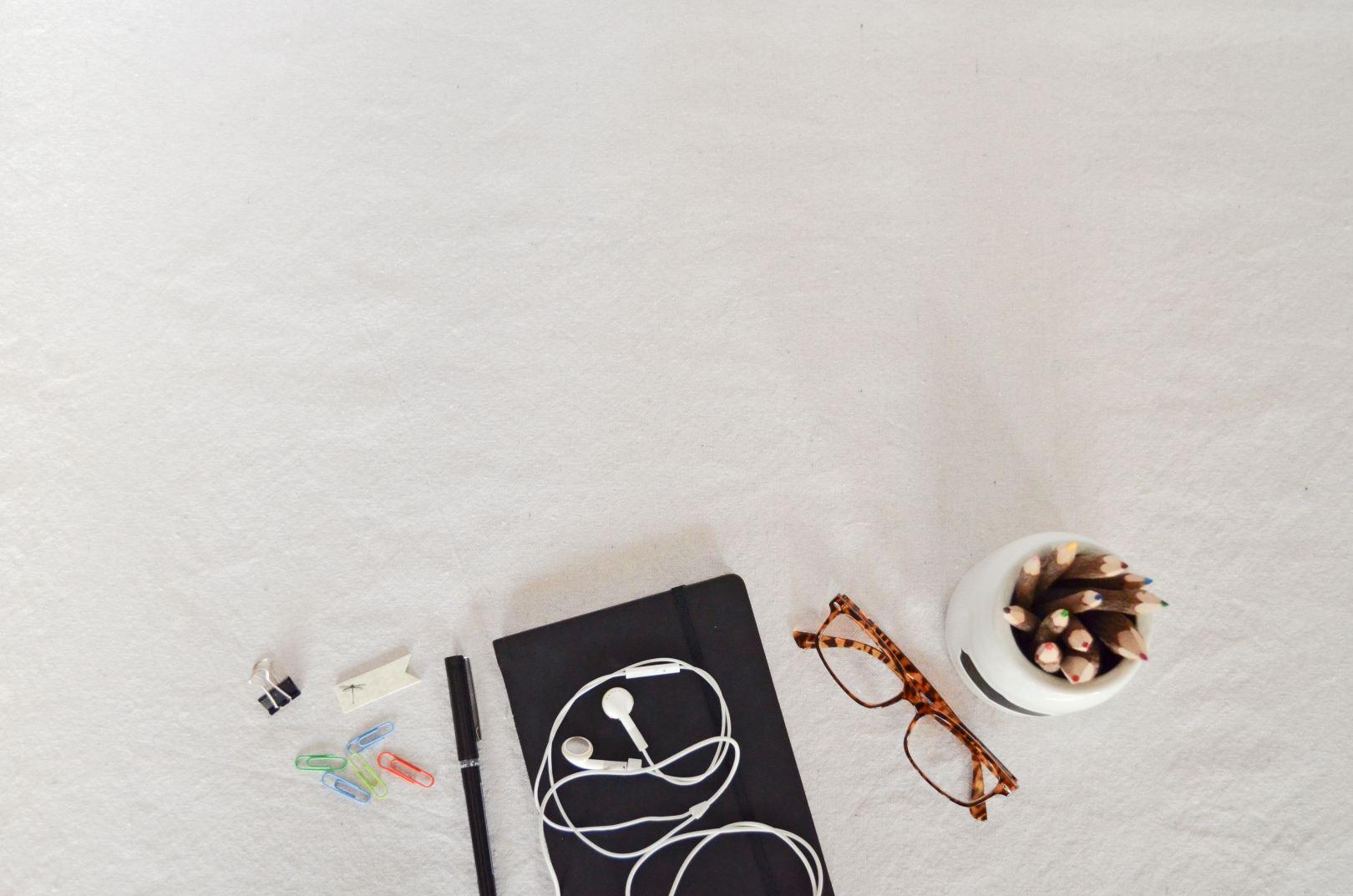 white desk notebook earbuds glasses pencils