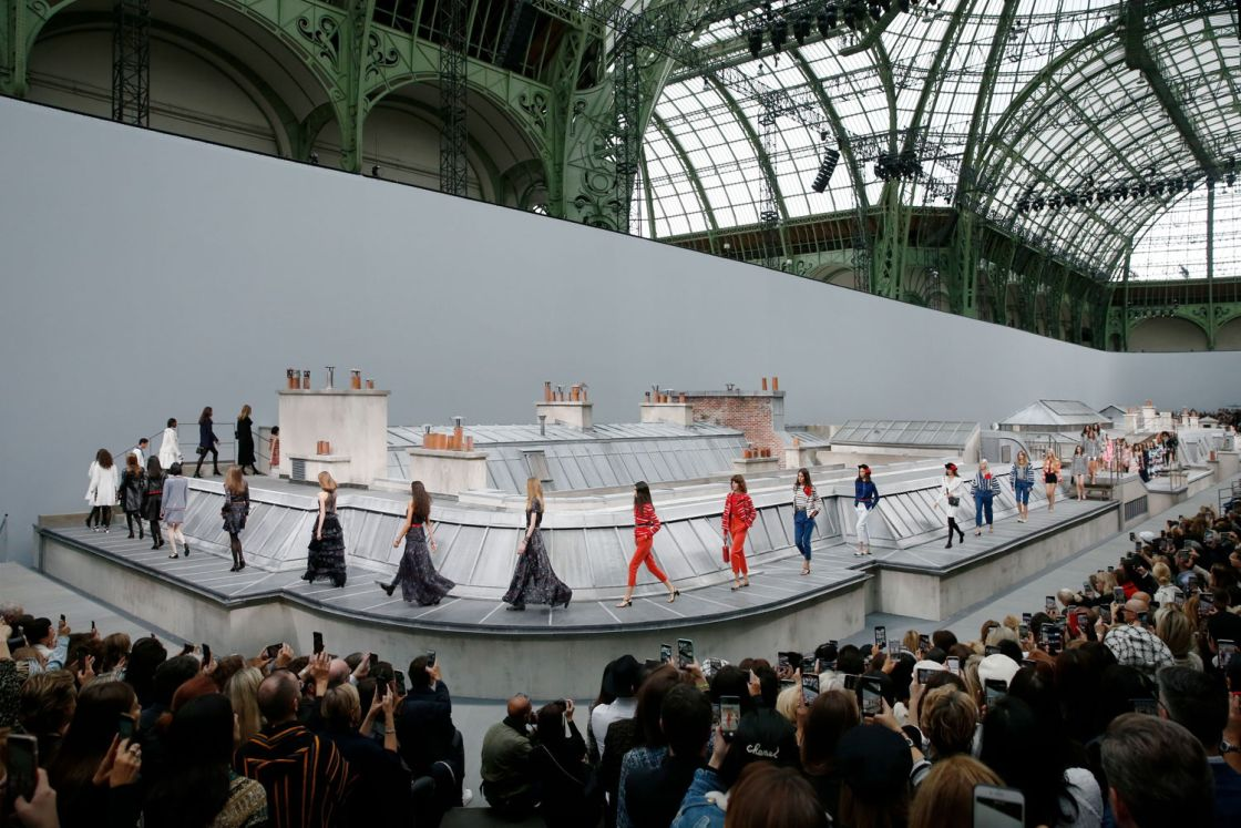 Chanel models walking the runway which looks like Parisian rooftops