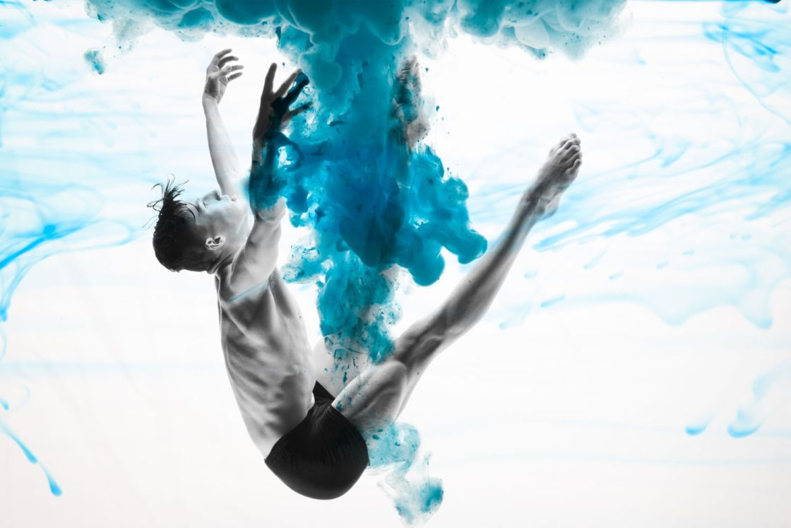 Male dancer jumping through the air with a blue swirl around him