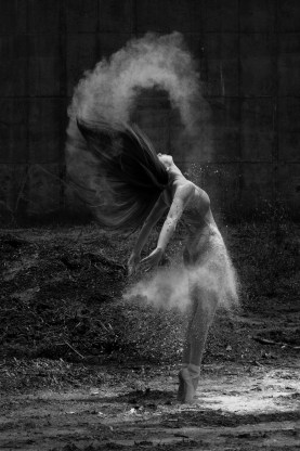 Female ballet dancer on pointe surrounded by powdery smoke