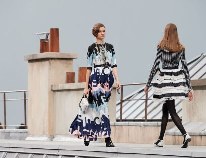 Model struts the runway for Chanel in a flowing pink, purple, blue and white dress