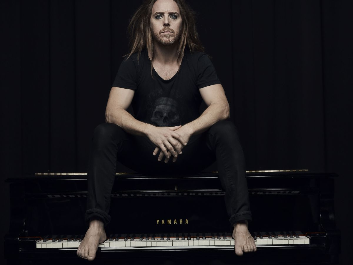 Musician and comedian Tim Minchin sits on top of a piano