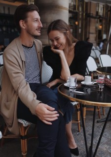 A man and woman sit outside a Paris cafe leaning in towards each other, with coffee cups on the table in front of them