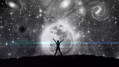 Image: A person, arms outstretched, in front of a starry sky