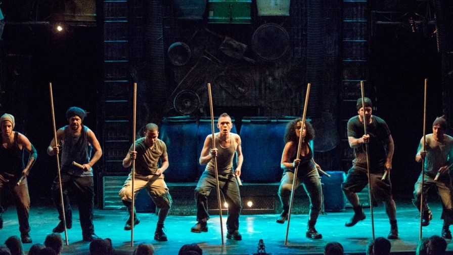Image: Stomp performance with all performers holding brooms