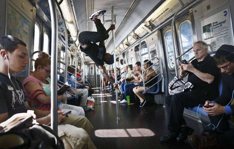 Image: Subway acrobat being mostly ignored by other passangers