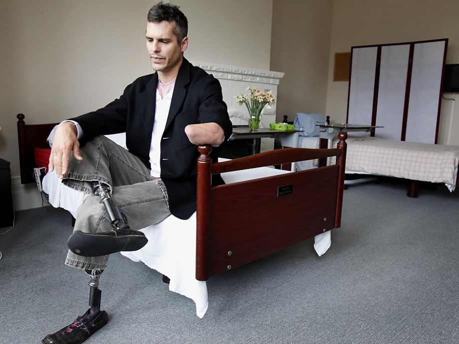 Image: Dr. BJ Miller sitting on a bed with his prosthetic legs visable