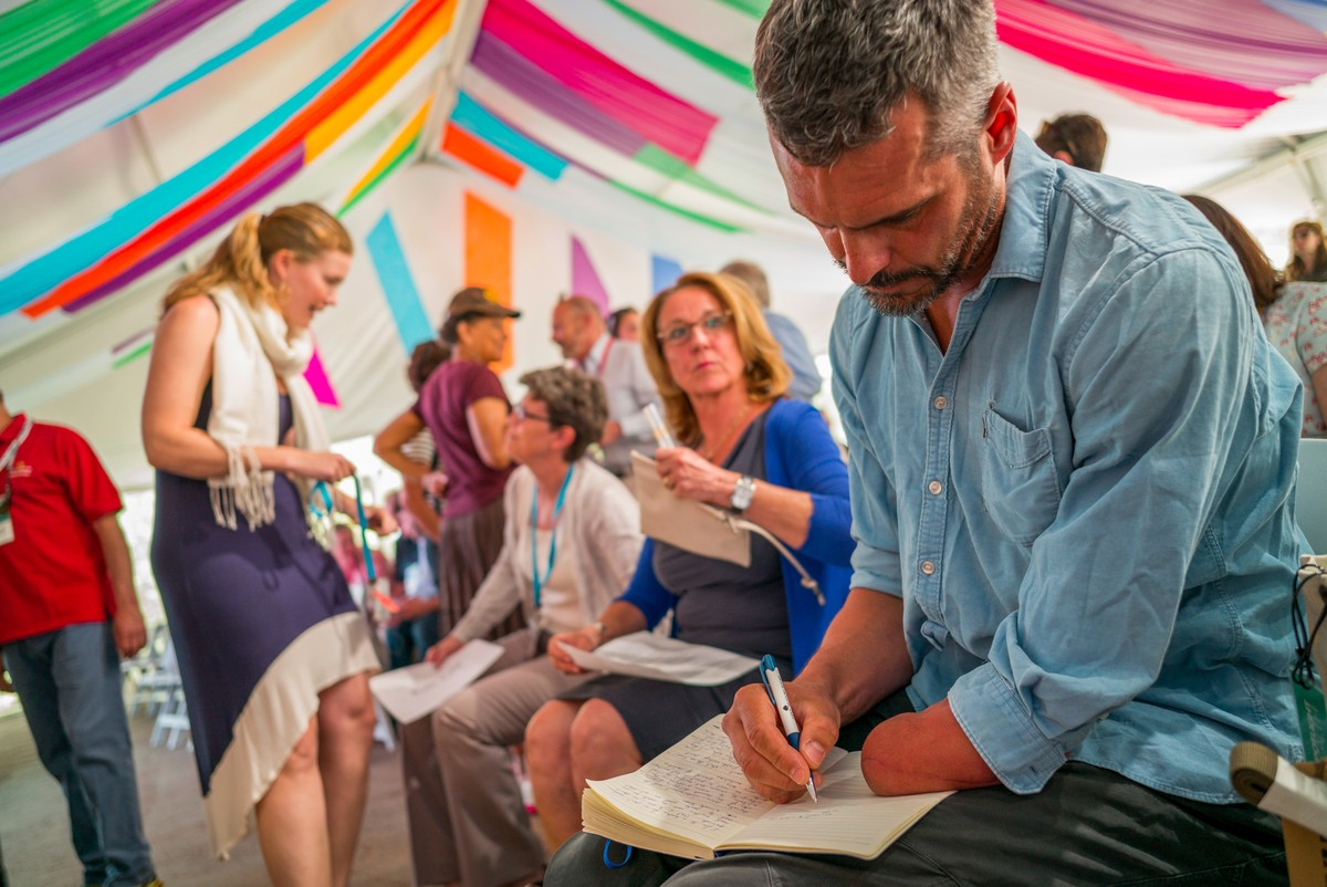 Image: Dr. Miller taking notes in a colorful tent