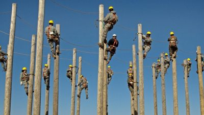 Image: Many telephone poles close together, each with a man at the top working.