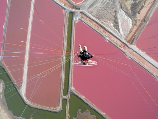 Image: Theo hanging from his paraglider, view from above, over salt flats of pink and green