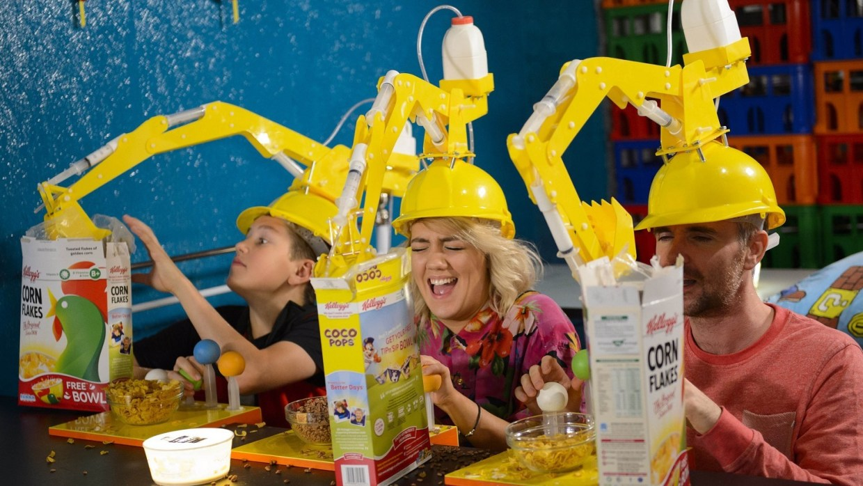 Jacob Tennet, Leah O'Connor and Martin Teall use Crane Head Cereal Serving Devices created by inventor Dominic Wilcox