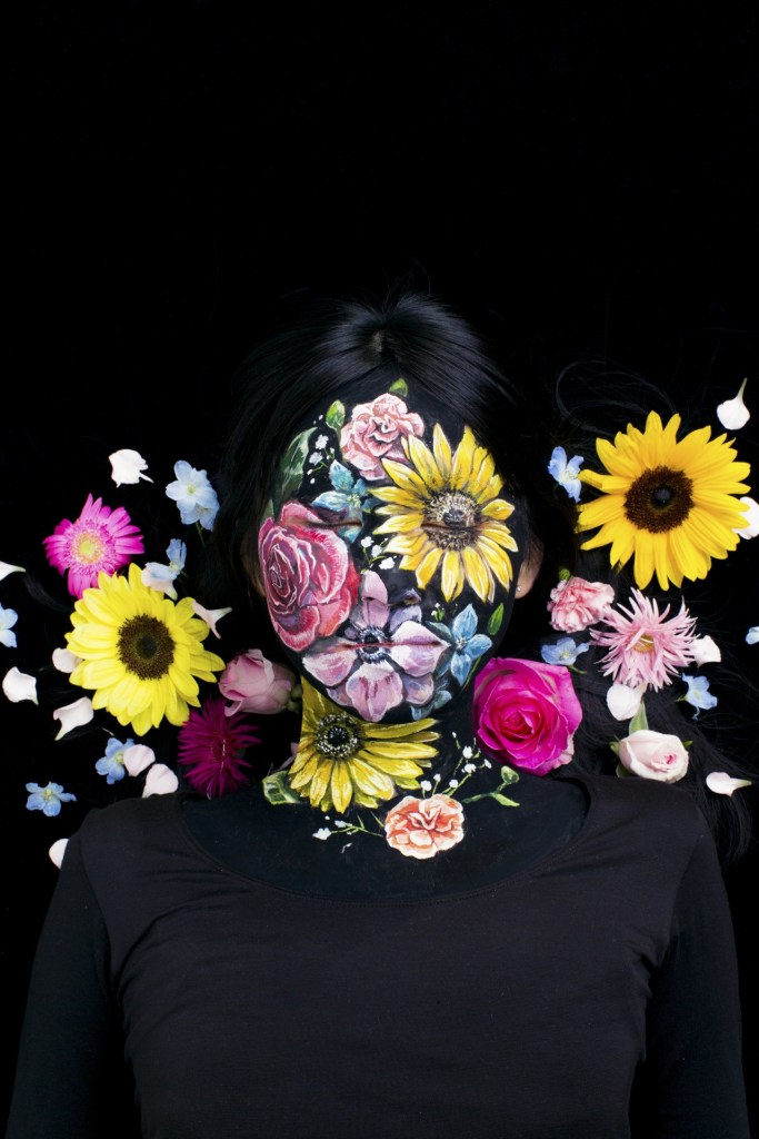 Image: Face painted with flowers to match flower background by Hikaru Cho