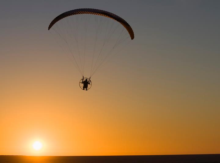 Image: Power paraglider in the air at sunset