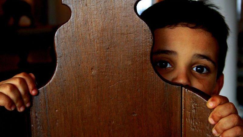 Image: Little boy hiding behind a chair