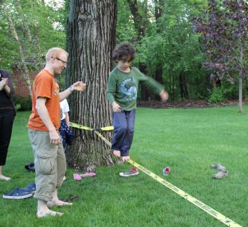 Image: A man helps a child learn to walk on the slackline