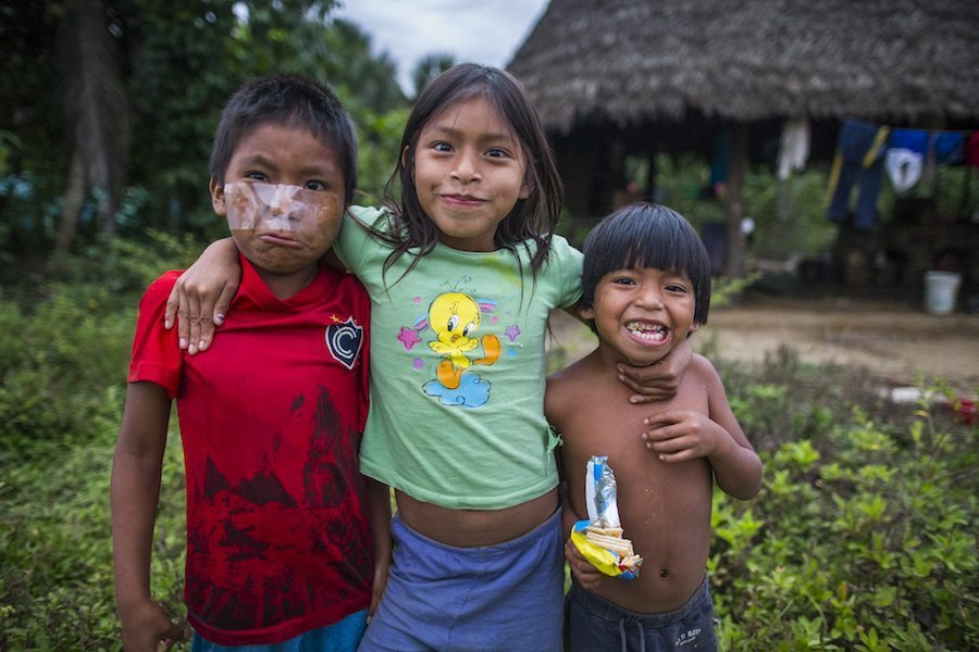 Image: Three kids from Manu National Park pose for photographer Charlie Hamilton James making funny faces