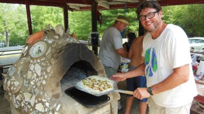 Image: Dr. Chuck inserting pizza into crazy pizza oven shaped like a fish