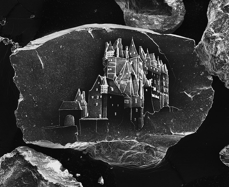 Image: An image from Vik Muniz series etching castles on grains of sand