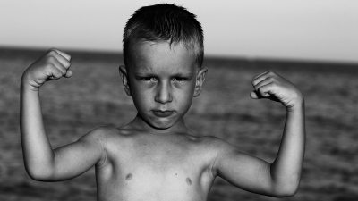 Image: Black and White photo of skinny kid making muscles