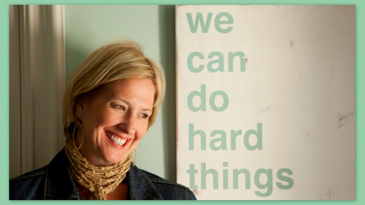 """Image: Brene Brown sitting before a sign that says, """"We can do hard things."""""""