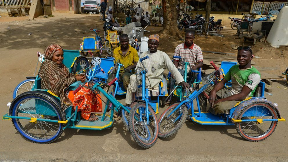 Image: Nigerians with polio sitting on their colorful bicycles that function like wheel chairs
