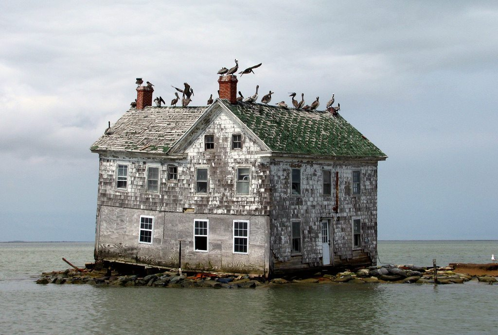 Image: Old house abandoned and falling into the sea