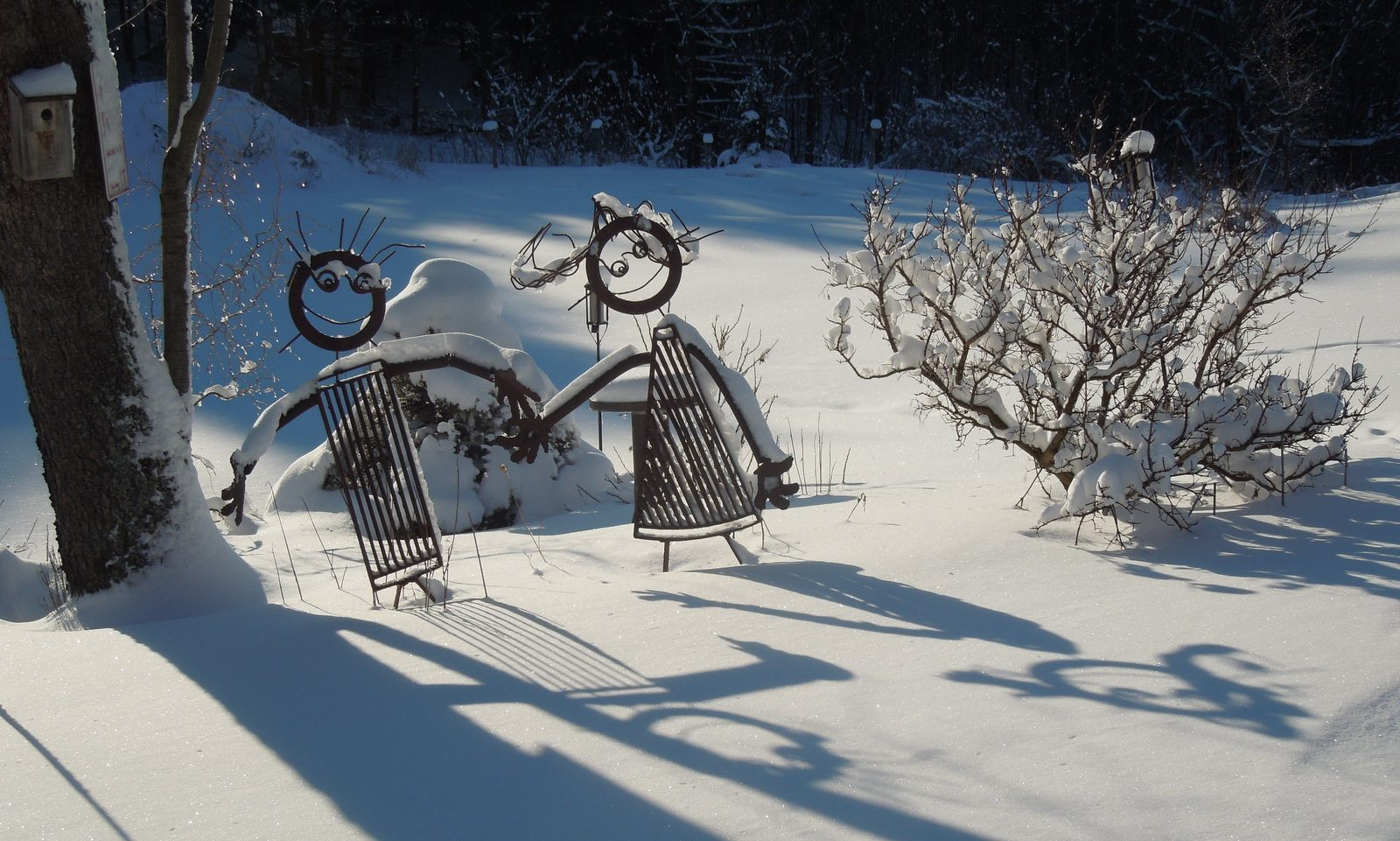 Image: Metal sculptures of two kids cast long shadows in the snow