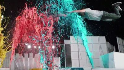 Image: Two OK Go band members flying through the air through paint splurting everywhere