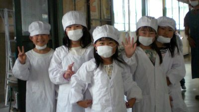 Image: Japanese 3rd graders in masks and hairnets smiling