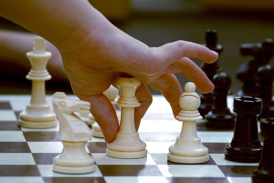 Image: Child moving a chess piece