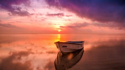 Image: Boat on a beach with the sunset in the background