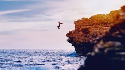 Image: Man jumping off of a cliff into water