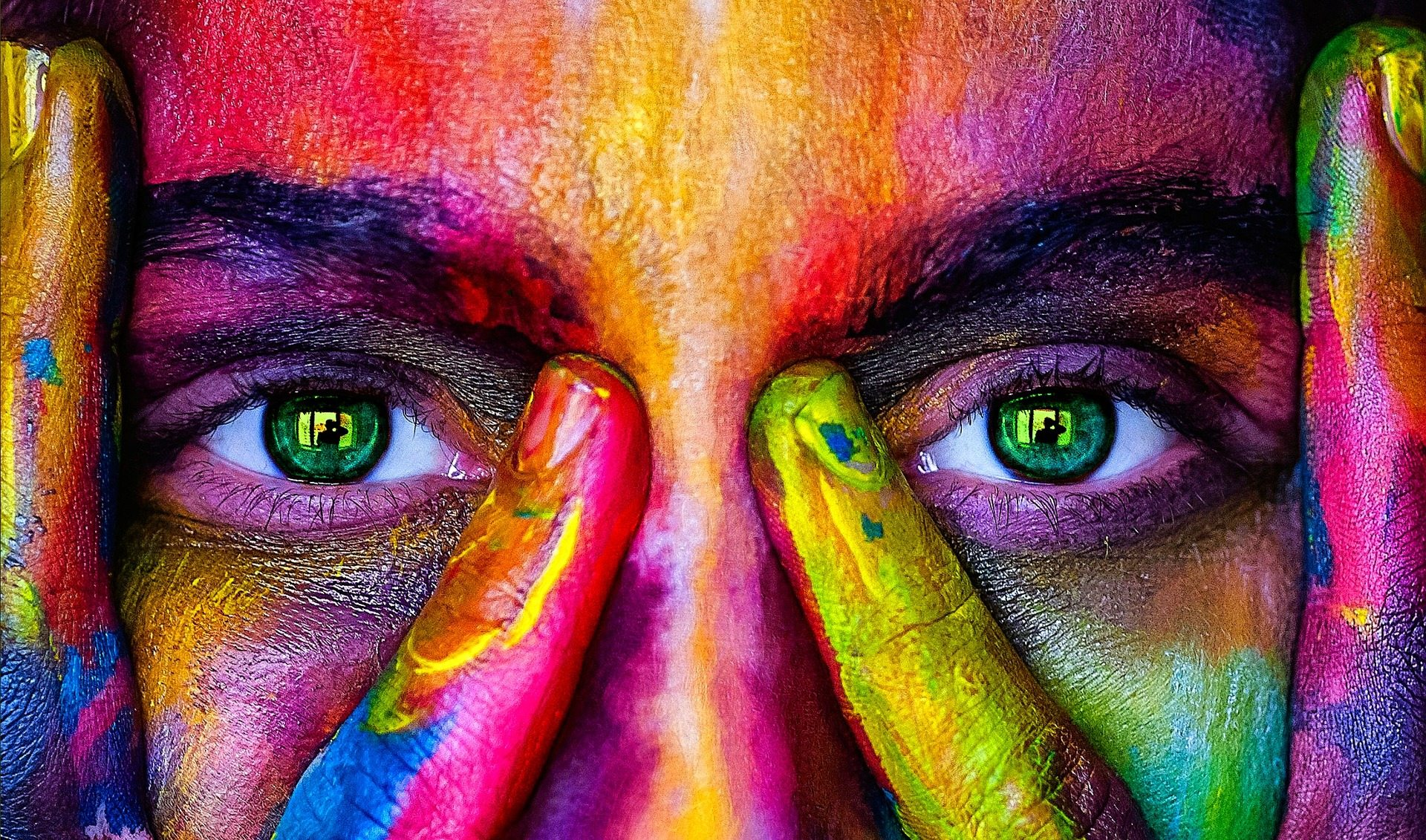 Image: Woman's face with brightly colored paint on it, indicating the new vision that this advanced technology will bring to peoples lives.