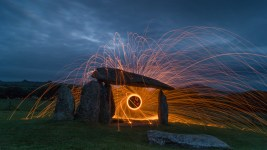 Image: At dusk, sparks fly out in radiating circles from under balancing boulders