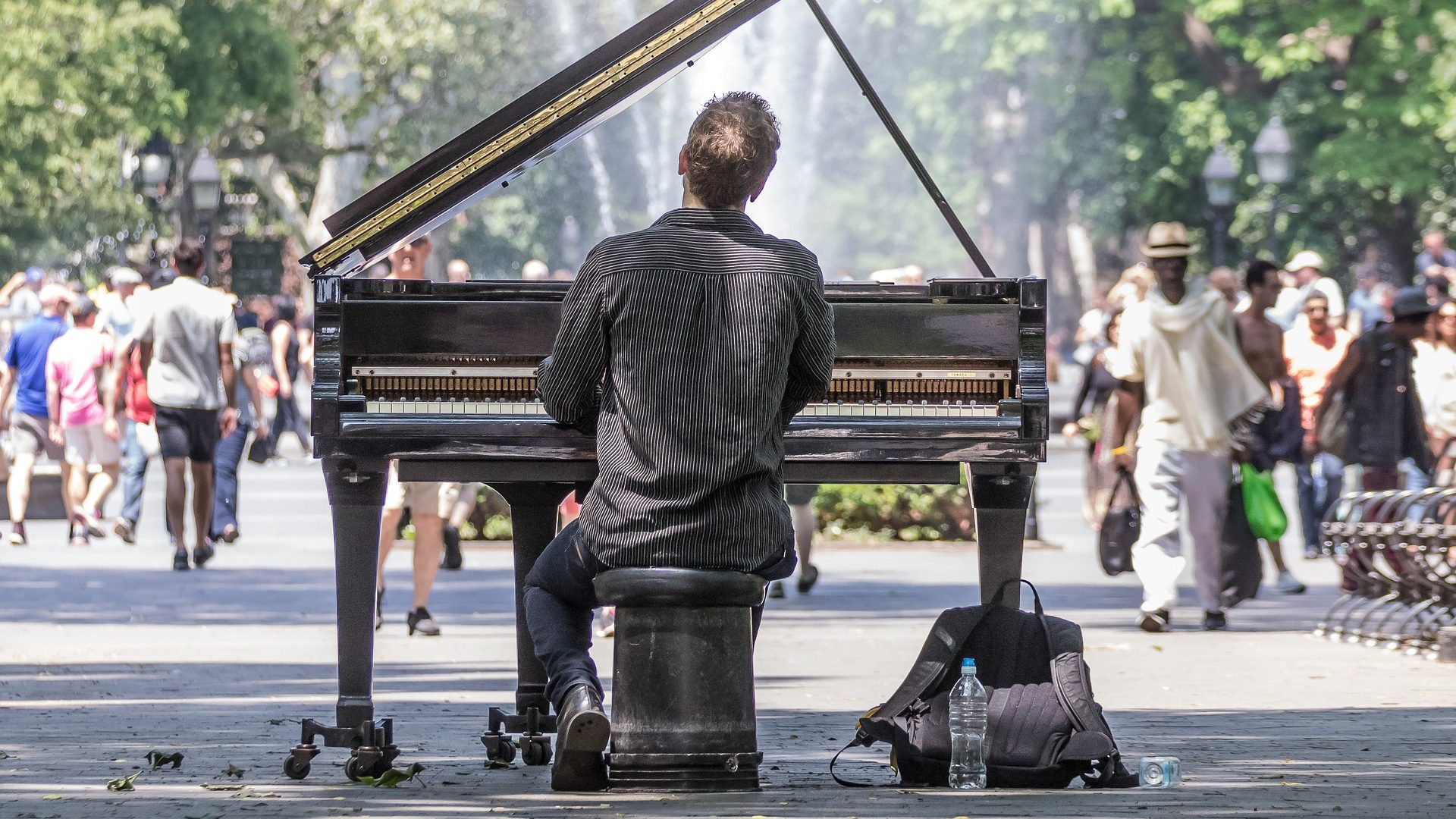 Image: Man playing piano in the middle of a park