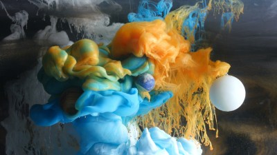 Image: Swirling clouds of colored ink in water colliding with miniatures of planets