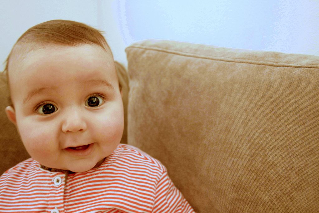 Image: Baby with wide eyes and stripe shirt on a couch